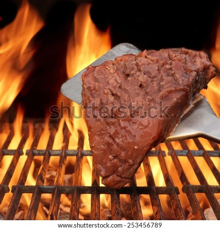 Flame Broiled Steak and Spatula on the BBQ Grill. Flames on the black Background.