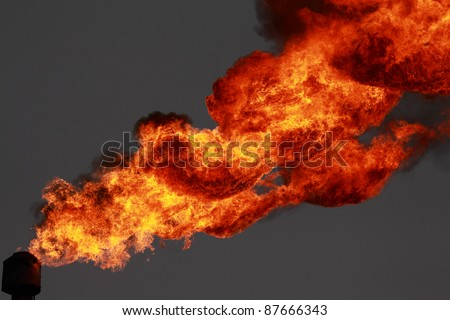 Flame from associated gas flaring in the atmosphere - stock photo