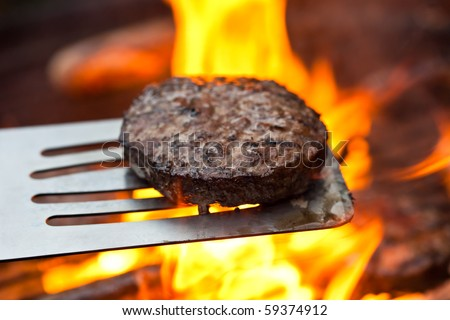 Flame grilled beefburger on a BBQ - stock photo