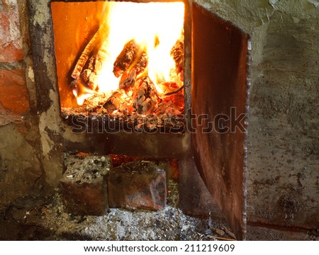 flame of burning wood in furnace with open door - stock photo