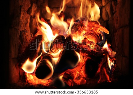 Flame on burning wood in fireplace - stock photo