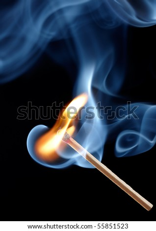 flame on matchstick with abstract smoke against black background