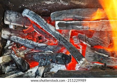 flame over hot wood-burning coals close up - stock photo
