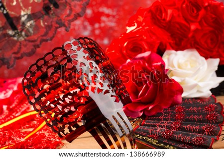Flamenco comb fan and roses typical from Spain Espana on red background - stock photo