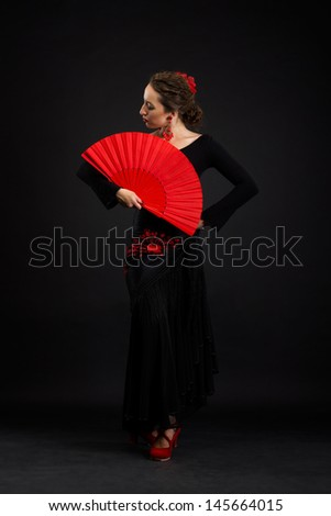 Flamenco dancer in black dress with red fan - stock photo