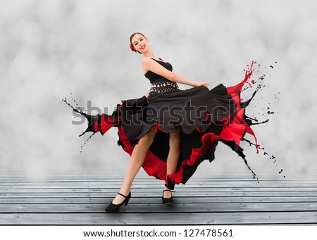 Flamenco dancer with dress turning to paint splashes on grey floorboard - stock photo