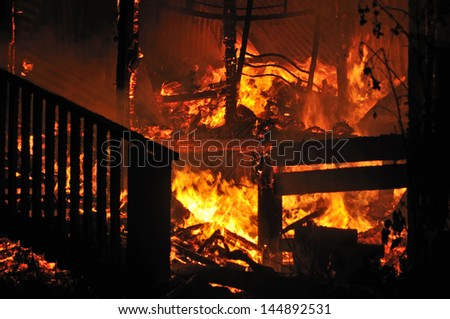flames and smoke rise from burning house - stock photo