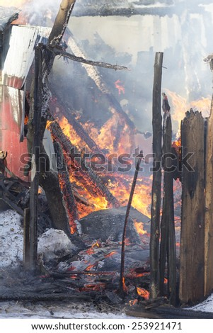 flames and smoke rise from burning wooden building