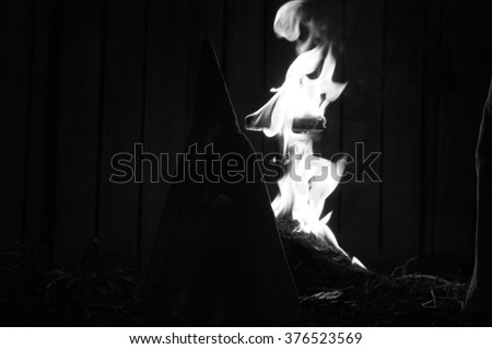 Flames engulf a burning cross at staged meeting of the Ku Klux Klan.  Silhouettes of hooded members who stand around the fire at night.  Black and white, documentary style with added film grain.