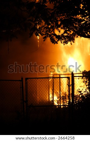 Flames engulfing the back of a house seen at night - stock photo