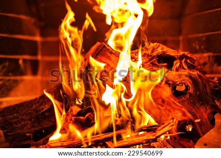 Flames in a fireplace on a brick wall background - stock photo