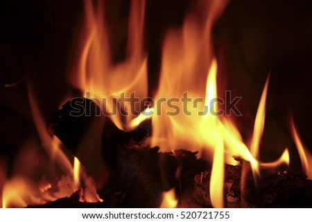 Flames of fire in a fireplace. Shooting horizontal with tones Orange and black.