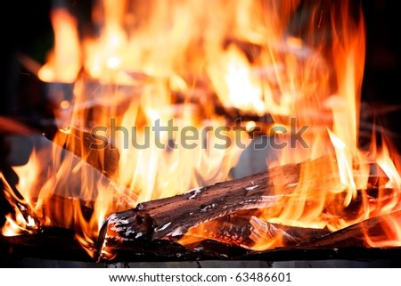 Flames shoot upwards from a raging outdoor log fire - stock photo