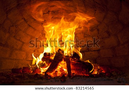Flaming Bonfire in front of brick wall - stock photo