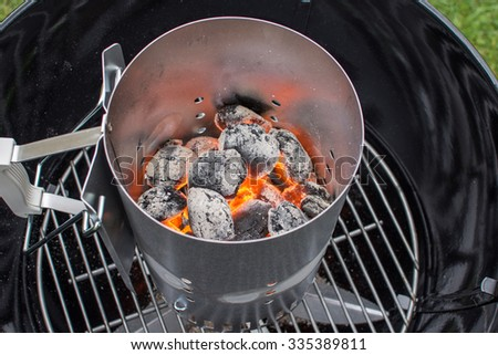 Flaming hot charcoal briquettes in a grill starter - stock photo