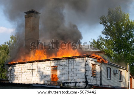 flaming house with clouds of smoke above it - stock photo