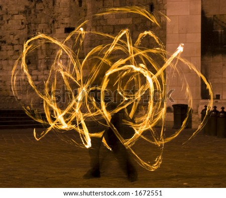 Flaming light blurs from the whirling baton on a fire dancing street performer. - stock photo