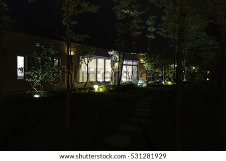 Flamingo Dai Lai, Vinh Phuc province, Vietnam - October 11, 2016 : beautiful living room of a villa overlooking the garden at night with the rocks on the grass at Flamingo Dai Lai resort