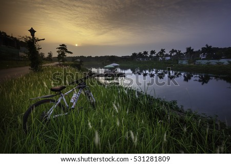 Flamingo Dai Lai, Vinh Phuc province, Vietnam - October 11, 2016 : bike beside the lake in the sunset, warm sunset view and beautiful clouds reflected in water at Flamingo Dai Lai resort