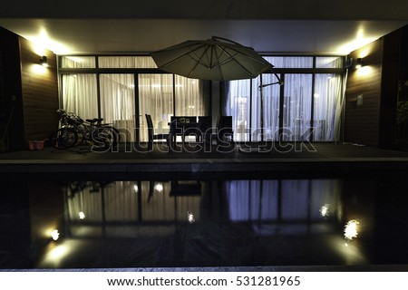 Flamingo Dai Lai, Vinh Phuc province, Vietnam - October 12, 2016 : the living room of a villa overlooking the beautiful pool in night with the reflection of water at Flamingo Dai Lai resort