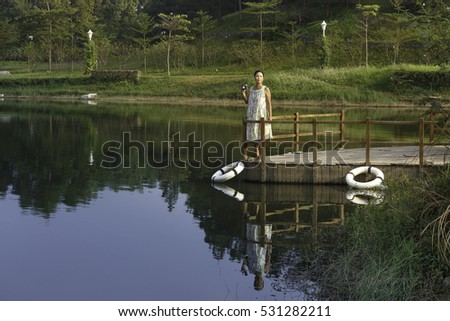 Flamingo Dai Lai, Vinh Phuc province, Vietnam - October 13, 2016 :woman standing on the dock watching the beautiful landscape of the autumn to take pictures, at Flamingo resort Dai Lai, Vietnam