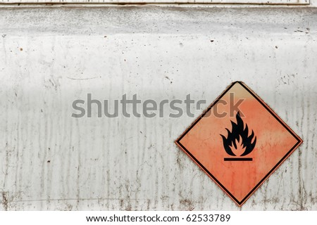 Flammable material weathered warning sign background. Fuel tank. - stock photo