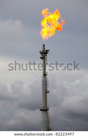 Flare burning gas at refinery plant - stock photo
