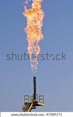 Flare burning natural gas to the atmosphere on an oil production platform - stock photo