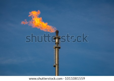 Flare of a coking plant with blue sky