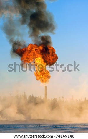 Flaring of associated gas during oil production. Pairs of snow around the torch. - stock photo