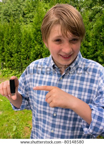 Flash drive  in  hand a teenage boy - stock photo
