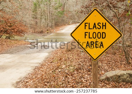 flash flood area sign with stream crossing behind it - stock photo
