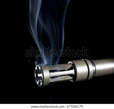 flash hider on an assault rifle that is still smoking - stock photo