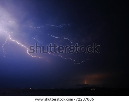 Flash in dark night sky over sea - stock photo