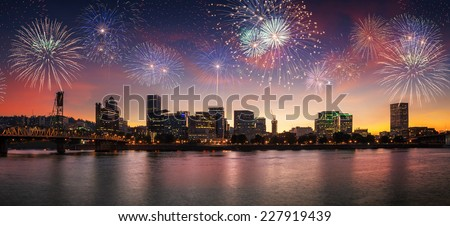 Flashing fireworks on a dramatic sunset sky with Portland, OR cityscape with Willamette river and Hawthorne bridge - stock photo