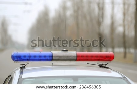 flashing indicators on a roof of the police car costs - stock photo