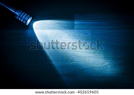 Flashlight and a beam of light in darkness. A modern led lamp with bright projection on dark wood table. Surface with copy space. - stock photo