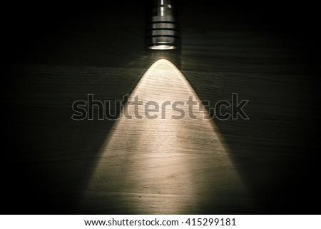 Flashlight and a beam of light in darkness. A modern led light with bright projection on dark wood table. Surface with copy space. - stock photo