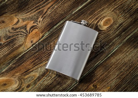 Flask alcoholic beverage on wooden background - stock photo