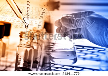 Flask in scientist hand and test tubes in rack  - stock photo