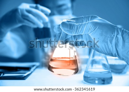Flask in scientist hand with blur scientist in laboratory  - stock photo