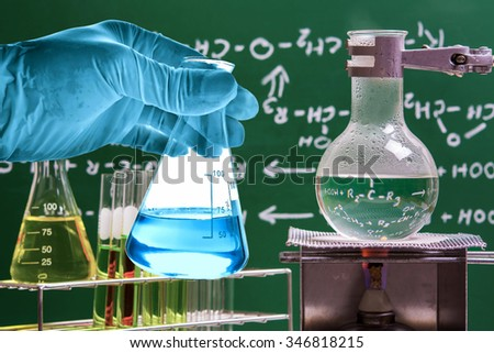 Flask in scientist hand with boiling liquid in round bottom flask