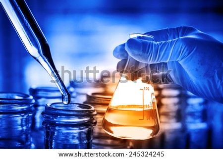 Flask in scientist hand with dropping chemical liquid to test tube - stock photo