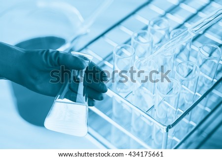 Flask in scientist hand with test tube in rack. Laboratory research, dropping liquid to test tube - stock photo