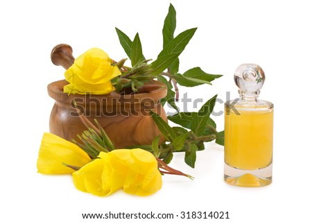 Flask of yellow bath supplement near evening primroses with mortar and pestle - stock photo