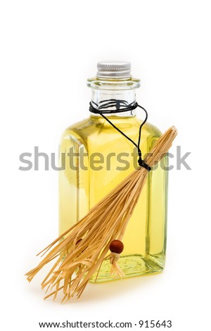 Flask of yellow oil with hay on white background