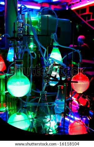 flask with colorful liquids on dark background - stock photo