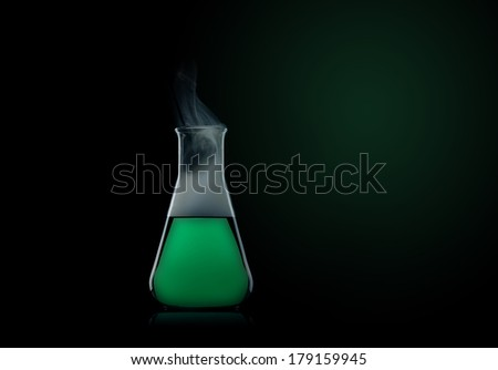 flask with green liquid to the black background  - stock photo