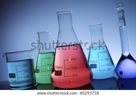 flasks group with color liquid and blue background - stock photo