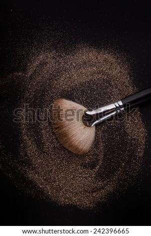 Flat blush brush with blush on it, loose powder and glitter blush, isolated on black backgrownd. - stock photo